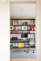 Fitted shelving with integrated desks and office chairs in study
