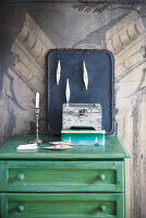Tin, wooden box, black tray with Christmas baubles and candle on top of green chest of drawers