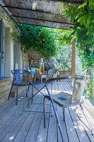Table and metal chairs on wooden terrace below pergola