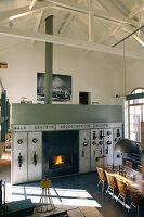 Altes Steuerpult mit Kamin als Raumteiler in umgebautem Loft