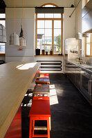 Kücheninsel mit Barhockern in umgebautem Loft mit Rundbogenfenster