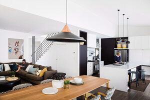 Schwarz-weiße Einbauküche, langer Esstisch und Lounge mit Polstersofa in offenem Wohnbereich