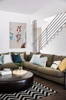 Polstergarnitur mit Kissen und Leder-Couchtisch vor Treppenwand