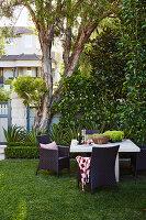 Tisch und Flechtstühle im Garten unter Baum