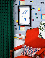 Roter Sessel vor Designertapete und Zeichnung in schwarzem Rahmen