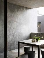Tisch mit Zimmerpflanzen und Designerhocker auf Balkon