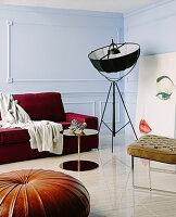 Dunkelrotes Sofa, Replik von Klassikerstehlampe, Beistelltisch Lederstuhl und Lederpouf im Wohnzimmer