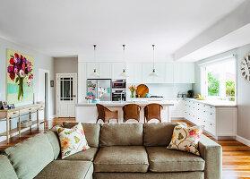 Polstergarnitur in offenem Wohnraum, im Hintergrund Küche mit Theke und Rattansesseln