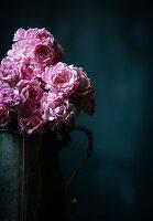 Vintage-style roses in metal jug