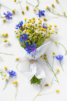 Blumenstrauss mit Kamillenblüten und Kornblumen, in Papier gewickelt