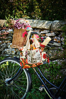 Flowers in wicker basket and baguette in floral shopping bag hung from bicycle