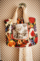 Floral shopping bag hung on hook on patterned wallpaper