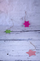 Paper Christmas stars of various colours on ribbons