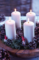Four pillar candles in wooden bowl festively decorated with moss, pine cones and gnome figurines