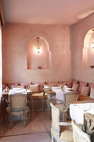 Oriental restaurant in shades of soft pink with lanterns in niches