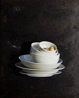 Quail eggs in stacked white bowls and plates against black background