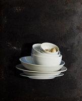 Stapel weißer Schalen und Teller mit Wachteleiern vor schwarzem Grund
