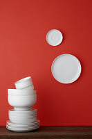 Stacked white crockery and two white plates on red wall