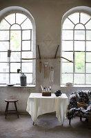 Tisch mit weißem Tuch vor einer Wand mit großen Bogenfenstern