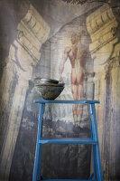 Stapel dunkler Schälchen auf einer blauen Leiter vor einem Wandbild