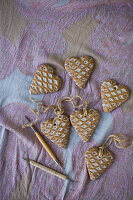 Heart-shaped pendants with waffle structure on pink patterned cloth
