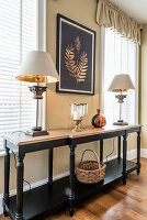Two table lamps on black console table in front of two windows