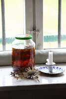 Jar of homemade St. John's wort oil for healing wounds on windowsill