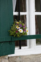 Posy of lady's mantle, red clover and ox-eye daisies on window shutter