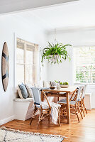 Dining table with corner bench and fern in hanging basket
