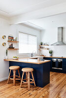 Wicker stools at counter in open-plan kitchen with wooden floor