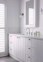 Weißer Waschtisch mit Marmorplatte und Holzfronten im Badezimmer