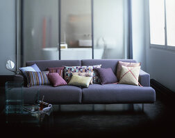 Cushions on lilac sofa in front of glass sliding door leading into bathroom