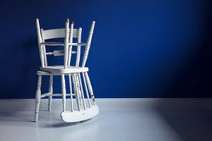 Zwei vermackte, weiße Windsorstühle vor blauer Wand