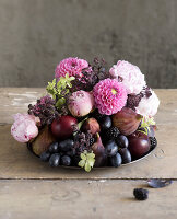 Pink and purple late-summer arrangement of fruit and flowers