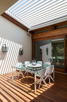 Dining table on terrace with sunlight falling through slatted roof