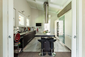 Masculine, modern kitchen with island counter and marble floor