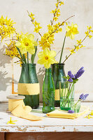 Spring arrangement of forsythia, narcissus and hyacinths in bottles and glasses