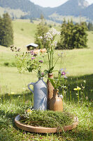 Rampion, lady's mantle, astrantia and marjoram in rustic stoneware jug and swing-top bottles