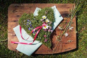 Herzförmiges Gesteck aus Blüten von Leinkraut, Frauenmantel, Majoran und Natterkopf