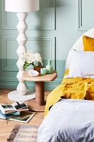 Nachttisch und weiße Stehleuchte vor mintgrüner Wand im Schlafzimmer