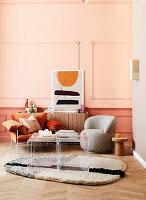 Designersessel und Plexiglas-Tischset im Wohnzimmer vor apricotfarbener Wand