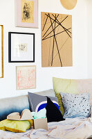 Framed picture and DIY cardboard pinboard above sofa with scatter cushions
