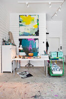 Malerstudio mit Schreibtisch und Vitnage grüner Servierwagen, Gemälde an weißer Holzwand