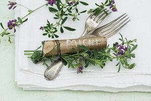 Besteck mit Haselnuss-Holz als Namensschild und Blauer Luzerne (Medicago sativa)