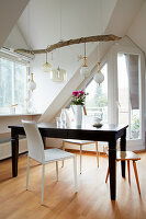 Various pendant lamps with cords wrapped around branch above dining table