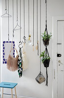 DIY coat rack made from black ropes and butchers' hooks against white wall