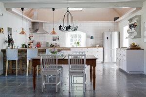 Esstisch vor der offenen Küche im Landhausstil mit schwarzem Boden