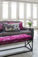 Graues Polstersofa mit bunten Kissen und Bank mit floralem Bezug