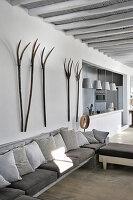 Heugabeln an der Wand über dem Sofa mit Kissen in Grautönen