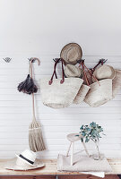 Straw hats, raffia baskets, feather duster and besom broom hung from coat rack